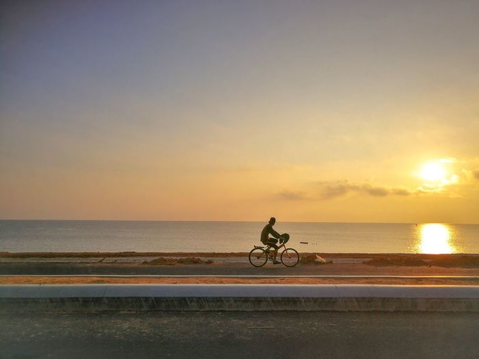 An unidentified cyclist and sunrise Kuala Terengganu Light Water Sea Full Length Sunset Pedal Beach Bicycle Silhouette Cycling Sand