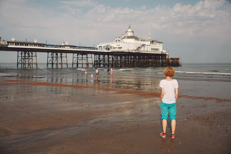 Rear view of woman standing by eastbourne pier at beach against sky