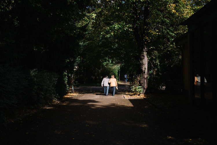 Rear view of people standing by trees