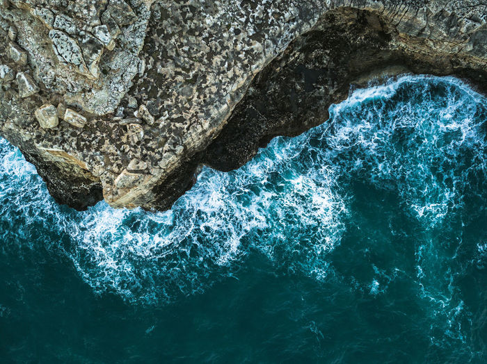 Rock Rock - Object Solid Sea Water Nature Rock Formation Beauty In Nature No People Sport Motion Waterfront Day Outdoors High Angle View Wave Geology Blue Rough Power In Nature Turquoise Colored Rough Sea View From Above Splashing Rock Formation Coastline