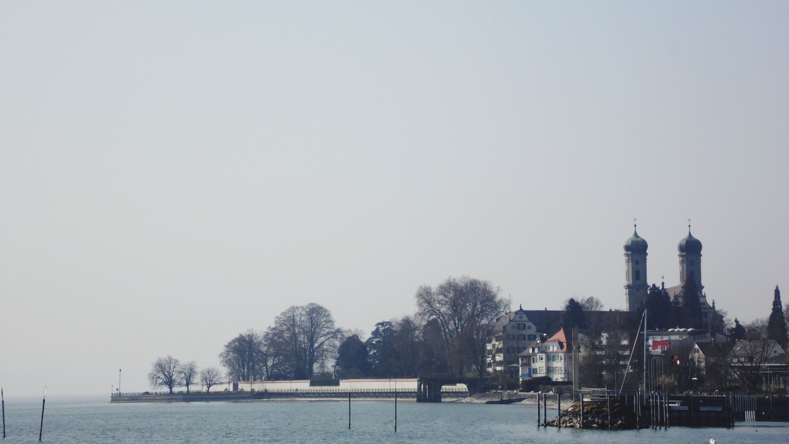 clear sky, water, built structure, waterfront, copy space, building exterior, architecture, tree, river, lake, nature, tranquility, winter, tranquil scene, bare tree, outdoors, nautical vessel, day, city, beauty in nature