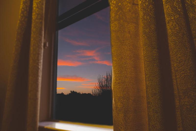 Close-up of orange sunset seen through window