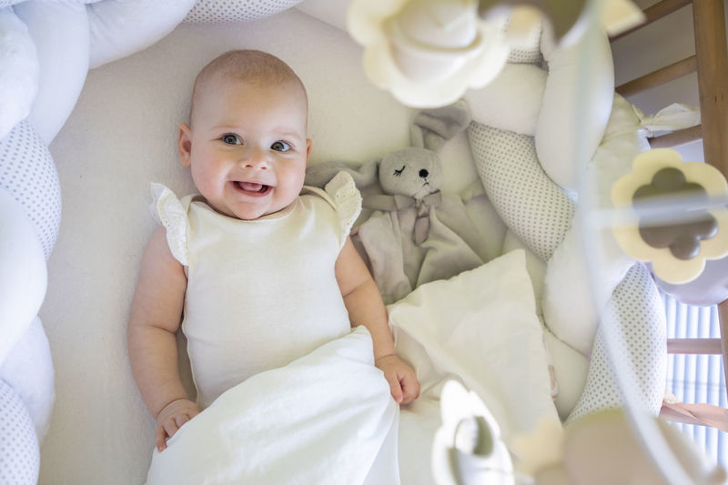 High angle view of cute baby girl lying on bed