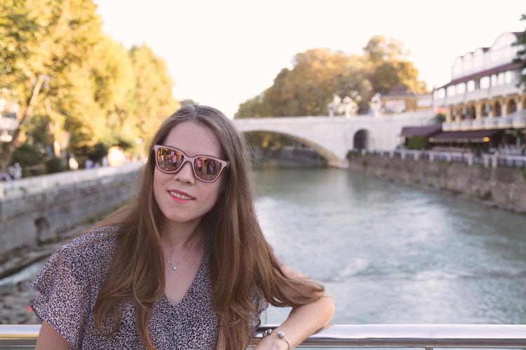 Portrait of beautiful woman wearing sunglasses standing on bridge over river