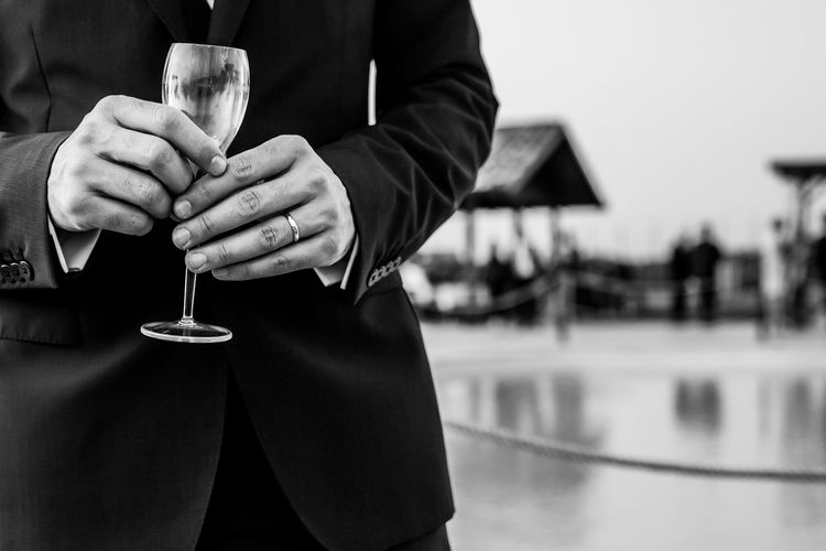 Midsection Of Bridegroom Holding Wineglass While Standing At Poolside