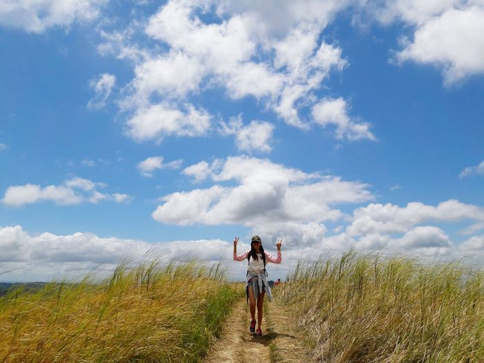 Full length of young woman showing victory sign on field against cloudy sky
