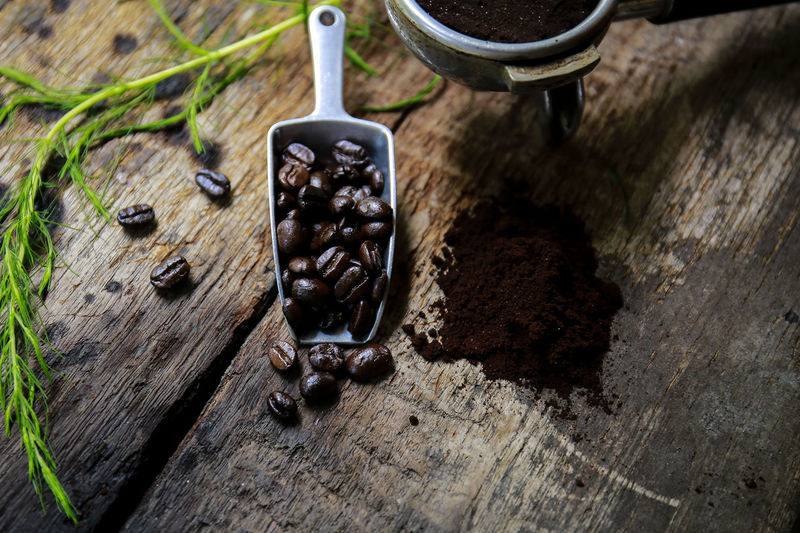 Coffee cup and coffee beans on wooden background. Top view. Black Color Brown Close-up Container Day Dirt Food Food And Drink Freshness Gardening High Angle View Kitchen Utensil Nature No People Outdoors Roasted Coffee Bean Selective Focus Still Life Table Wood - Material