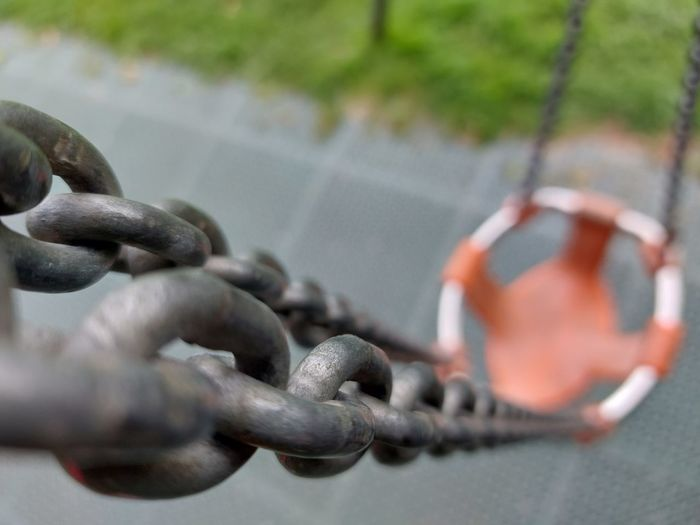 Close-up of metal chain against fence