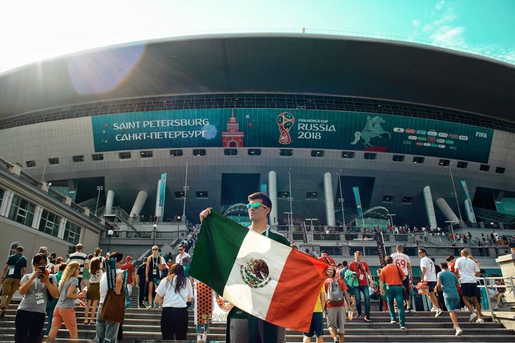 Young man with mexican flag standing outside stadium
