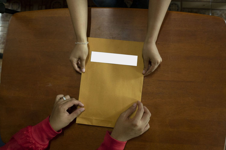 Directly above shot of cropped hands holding envelope at table