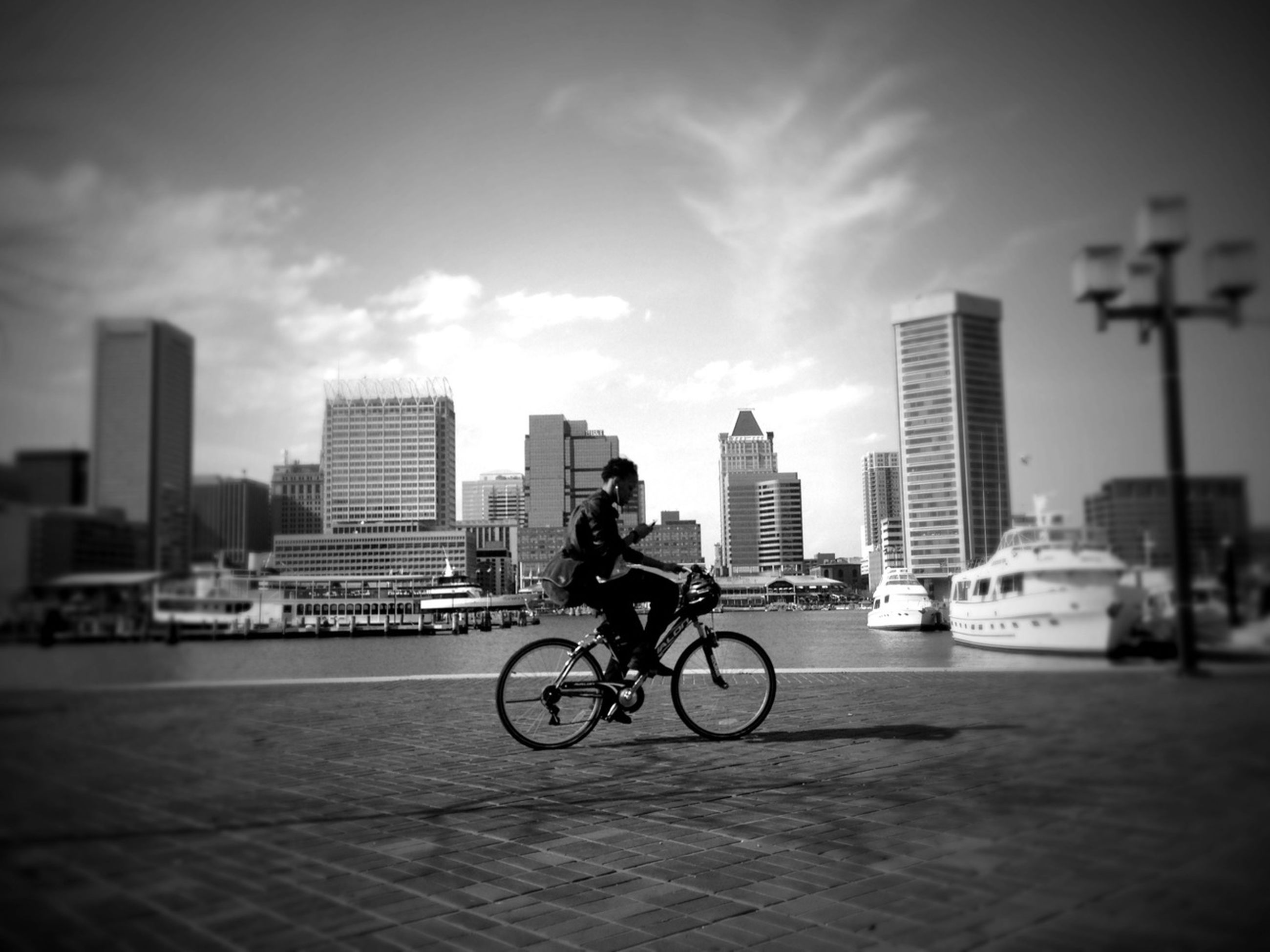 bicycle, building exterior, land vehicle, city, transportation, architecture, mode of transport, built structure, street, riding, city life, road, sky, car, full length, men, skyscraper, cycling
