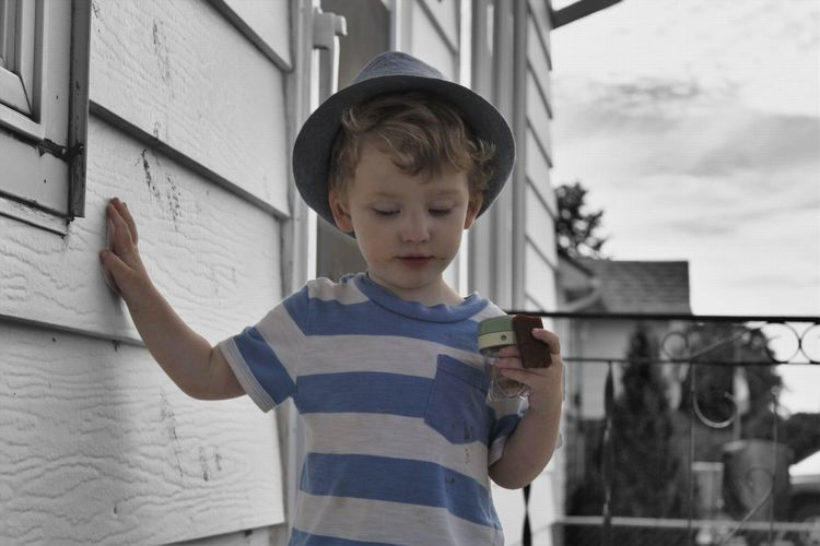 Boy in hat holding toy outside house