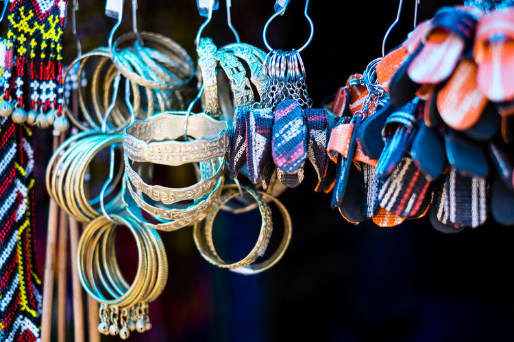Close-up of bracelets and key rings for sale at street market