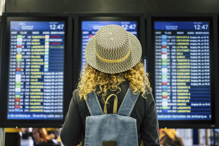 Rear view of woman wearing hat while standing at airport