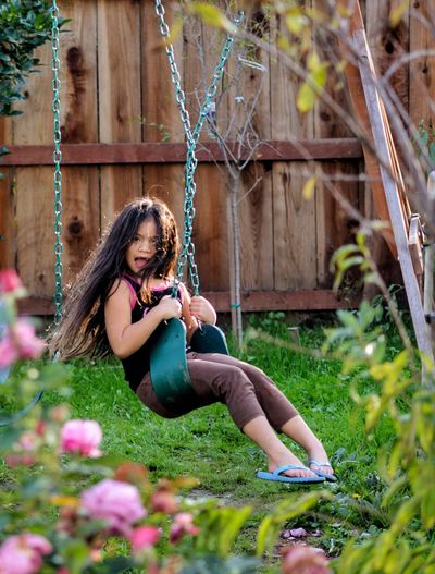 Girl playing on swing against fence at yard