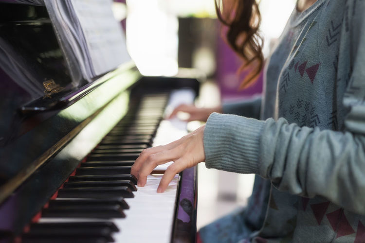 Midsection of woman playing piano while sitting at home