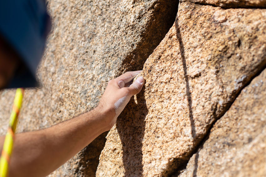 Close up hand of young man climber in a crack while climbing a wall on a sunny day. Close Up Hand Cliff Climbing Climb Holding Powder Handhold Rock Young Mountain Hanging Strong Finger Outdoor Sport Stone Grip Difficult Exercise Magnesium Athlete Mountaineer Leisure Activity Magnesia