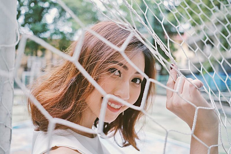 Portrait of smiling woman seen through net