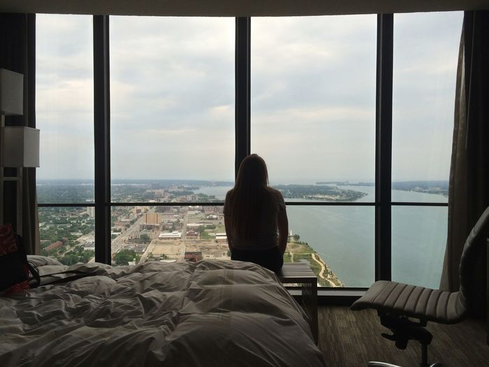 Rear View Of Woman Standing In Hotel Room Against Window