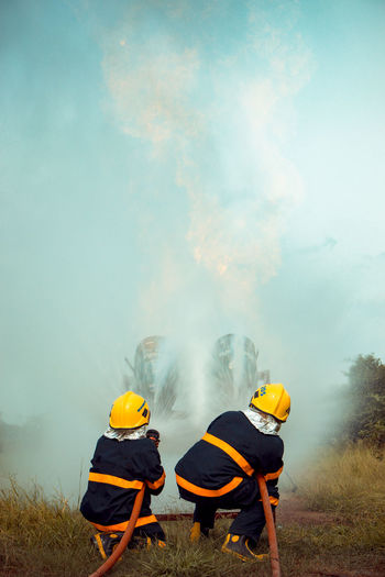 Firefighters Spraying Water While Crouching On Field