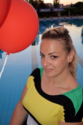 Portrait of woman with balloon by swimming pool
