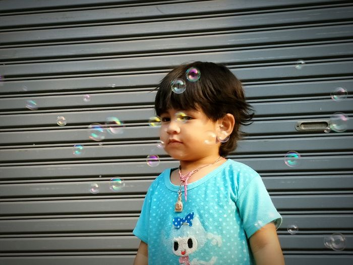Cute girl playing with bubbles against shutter