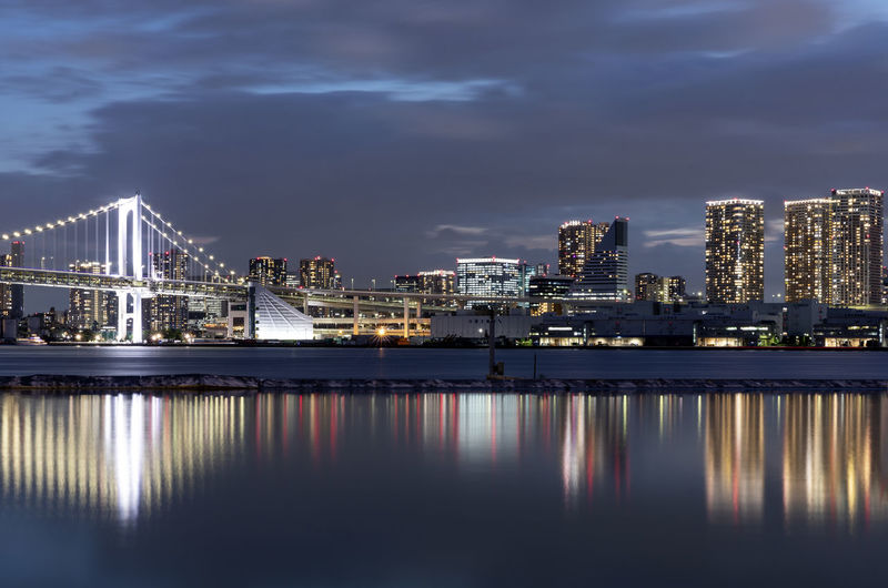 Illuminated city by river against sky