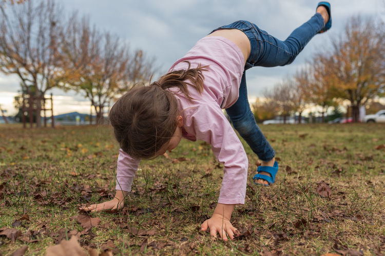 Full length of girl practicing handstand on playing field