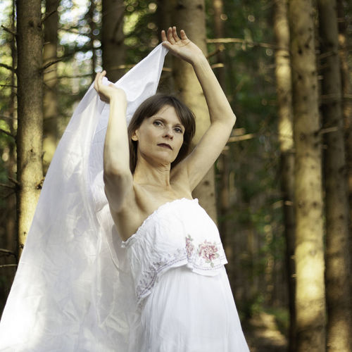 Midsection of woman standing against trees in forest
