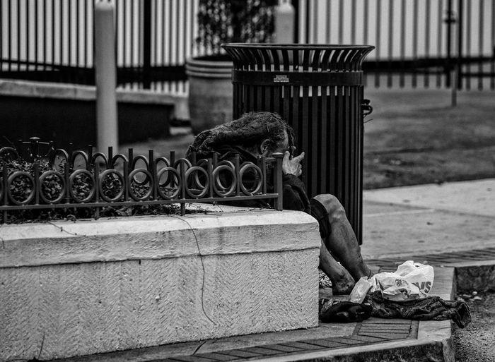 Beggar sitting on sidewalk