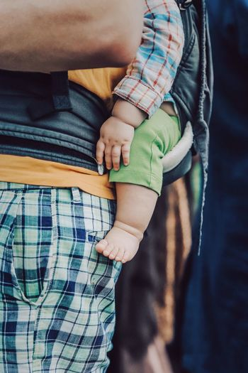 Midsection of father carrying baby