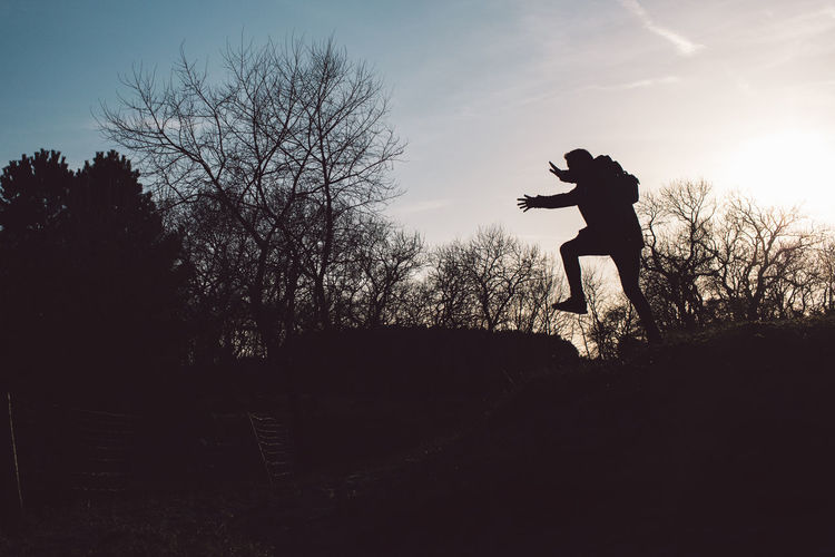 Silhouette man jumping on bare tree against sky
