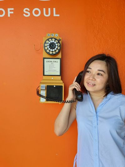 Portrait of smiling woman standing against orange wall