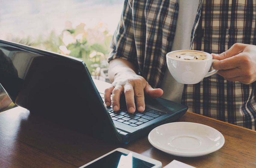Male using a computer with coffee cup on wooden table. Wireless Technology Technology Cup Connection Computer Laptop Drink Mug Coffee - Drink Coffee Cup Communication Coffee Food And Drink Table One Person Real People Refreshment Midsection Adult Lifestyles Using Laptop Hand Crockery