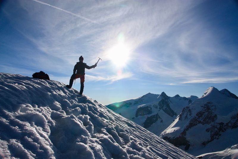 Low angle view of man standing on snowcapped mountains against sky
