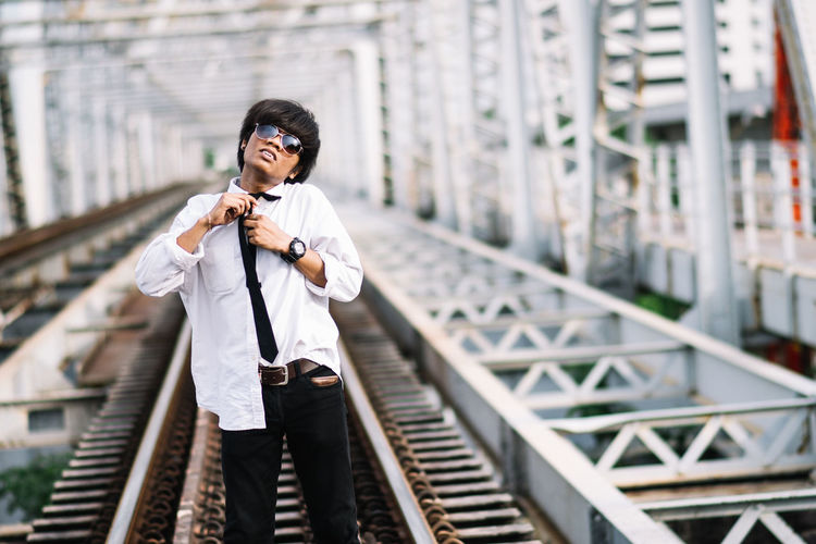 Portrait of young man getting dressed while standing on railroad track