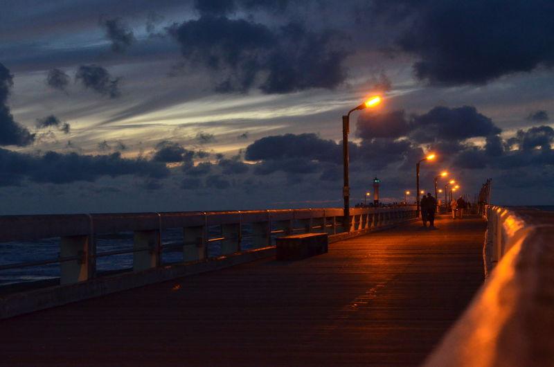 Illuminated pier over sea against cloudy sky at dusk