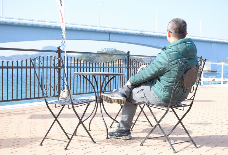 Rear view of man sitting on chair against railing