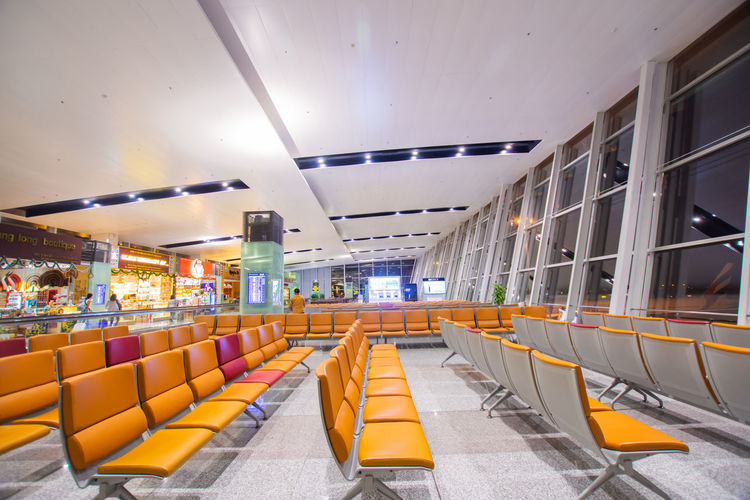 Illuminated Seat Indoors  Chair Ceiling Absence Architecture Empty No People Modern Built Structure Airport Transportation In A Row Sign Lighting Equipment Large Group Of Objects Yellow Arrangement Architectural Column