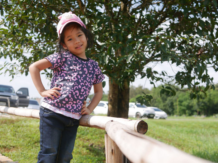 Portrait of cute girl standing against tree