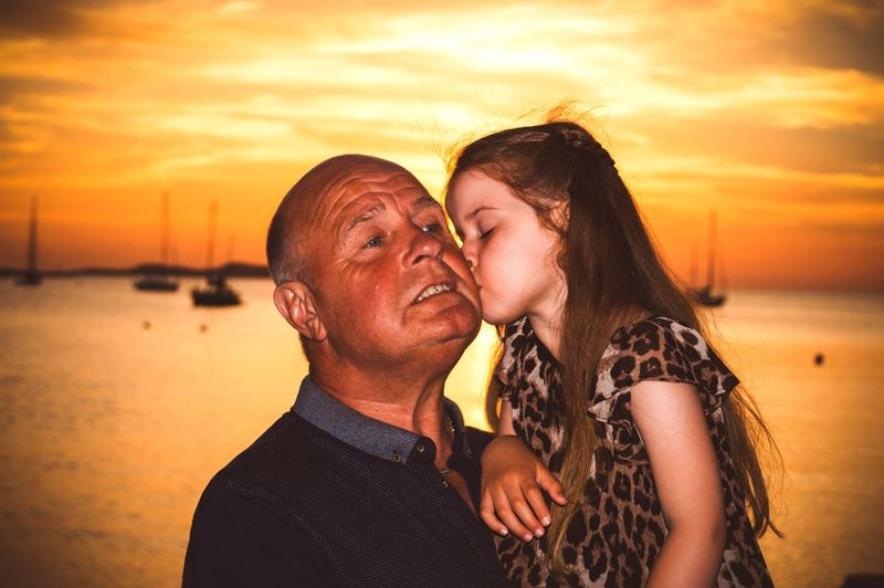 Girl kissing grandfather while standing at beach during sunset