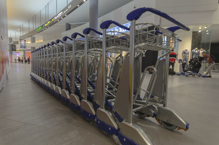 Luggage trolley at airport. Airport Airport Trolley Baggage Claim Floor Indoors  International Luggage Luggage Cart  Luggage Trolleys Luggage, Travel  Motion People Pushing Sign Signage Trolley Waiting