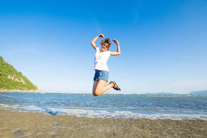 Beach Beautiful Woman Beauty In Nature Blue Clear Sky Day Full Length Happiness Horizon Over Water Jumping Leisure Activity Lifestyles Mid-air Motion Nature One Person Outdoors Real People Scenics Sea Sky Smiling Water Young Adult Young Women