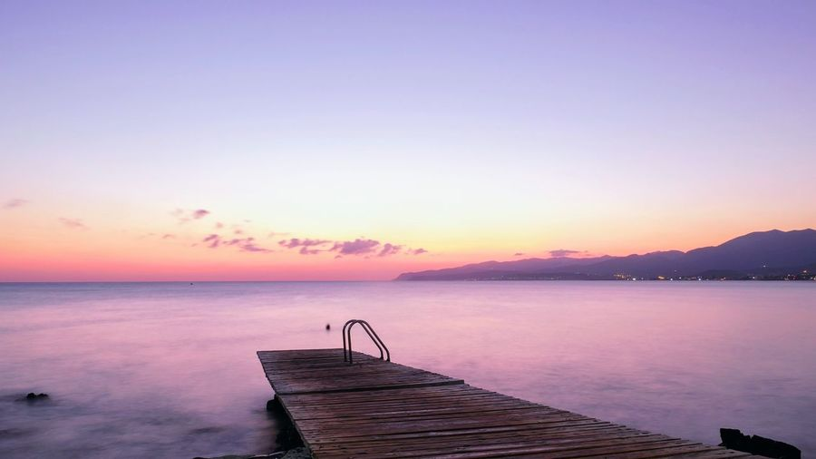 Pier over sea against sky duriduring sunset