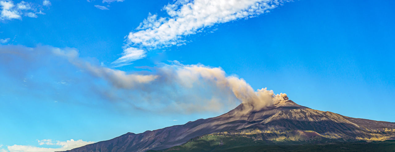 Panoramic view of volcanic mountain against blue sky