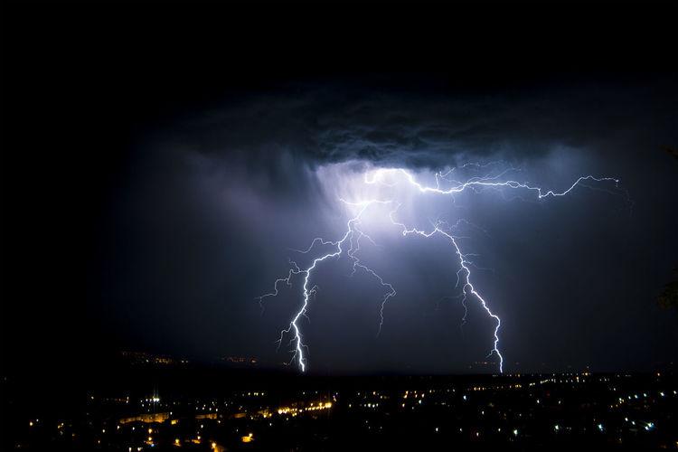Lightning Over Cityscape Against Sky At Night