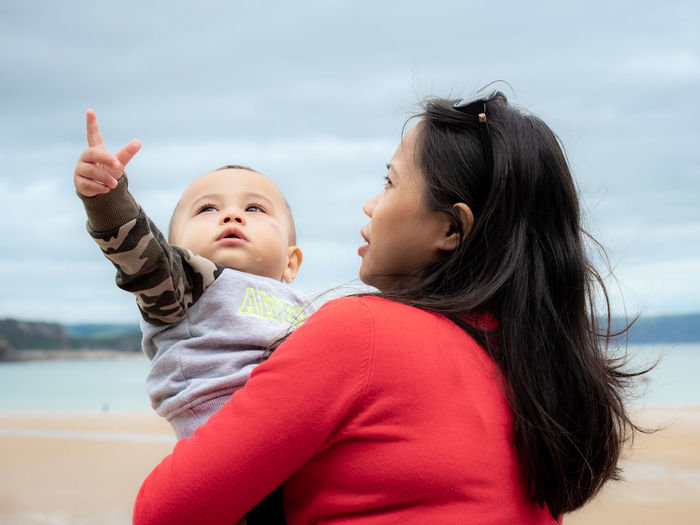 Mother carrying cute daughter while standing at beach against sky