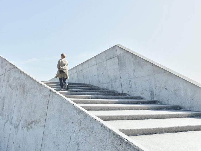 Man standing on staircase against clear sky