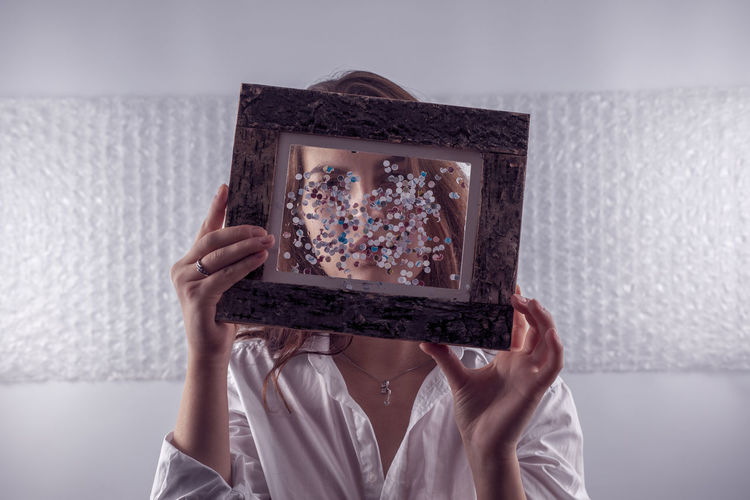Woman Covering Face With Picture Frame At Home