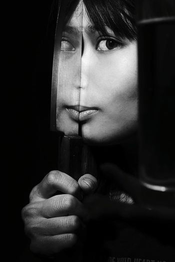 Portrait of woman holding kitchen knife with reflection against black background